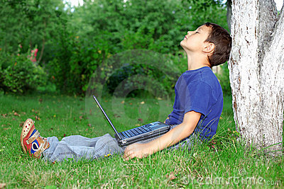 Boy with notebook sit at tree