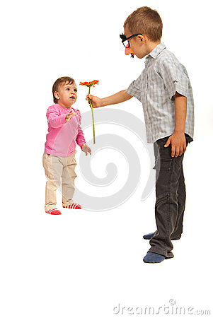 Boy offering flower to small girl