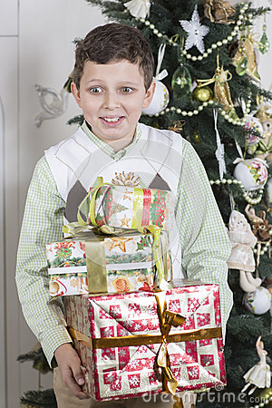 Boy is overwhelmed with many Christmas gifts