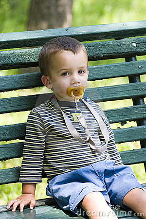 Boy with pacifier on bench