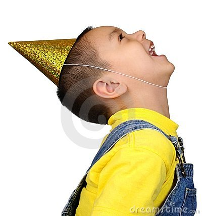 Boy in party hat looking up laughing