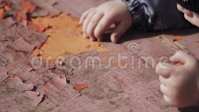 Boy peels old paint. Off the table with his hands stock video footage