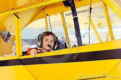 Boy in Piper Cub airplane wearing headset