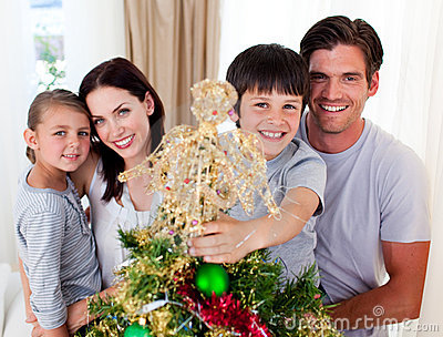 Boy placing a Christmas star on the top of a tree