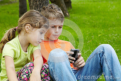 Boy play electronic game, sister sits next to him