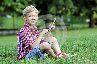 Boy play with tablet pc in park