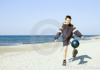Boy playing ball on beach.