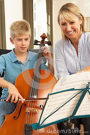 Boy playing cello in music lesson