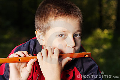 Boy playing flute in dark forest