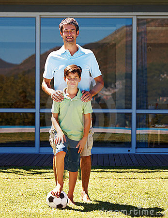 Boy playing football with his dad
