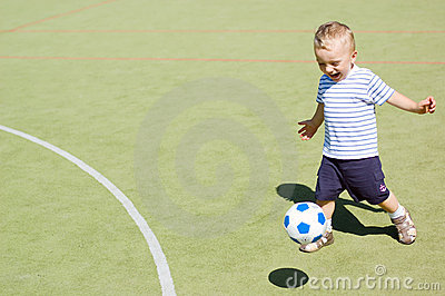 Boy playing football stadium