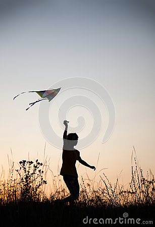 Free Boy Playing Kite On Summer Sunset Meadow Silhouetted Stock Photo - 98390760