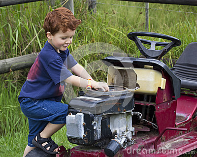 Boy playing outside with broken tractor