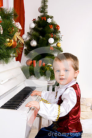 Boy playing the piano on eve of Christmas