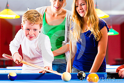 Boy playing pool billiard with family