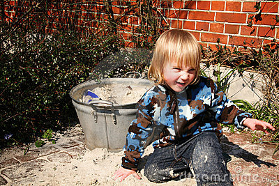 Boy playing beside sand box
