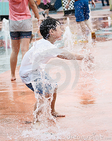 Boy playing with spraying water