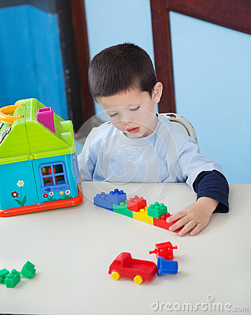 Boy Playing With Toys At Desk In Preschool