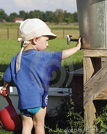 Boy playing at water barrel