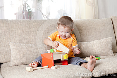 Boy playing with wooden building toys at home