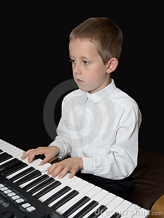 Boy plays keyborad, piano, looking in notes sheet