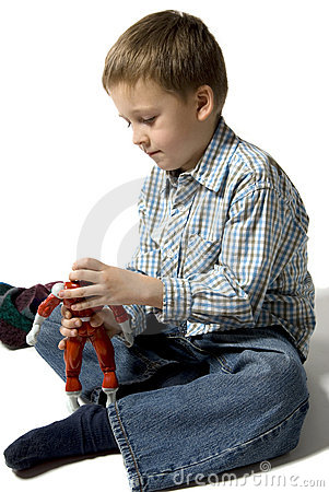 The boy plays with the robot
