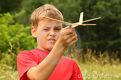 Boy plays with wooden airplane on nature