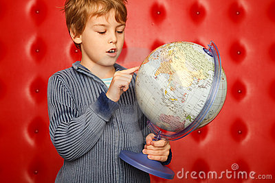 Boy pointing finger on globe. Portrait on red