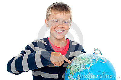 Boy pointing out a continent on the globe