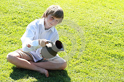 Boy pooring water from a pitcher