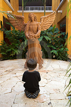 Boy praying in front of an angel