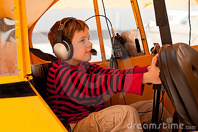 Boy pretends to fly Piper Cub airplane