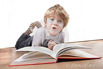Boy pulling a funny face whilst reading book
