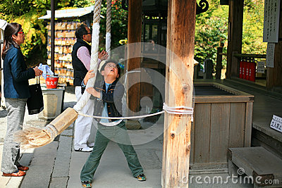 Boy pulls rope to ring a bell at Kinkakuji temple Editorial Image