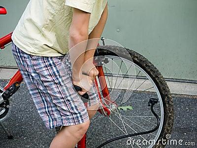 Boy pumping up a bike tire