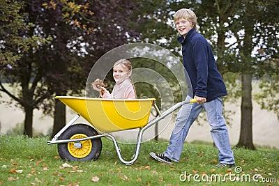 Boy pushing girl in wheelbarrow