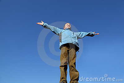 Boy raises his arms to blue sky