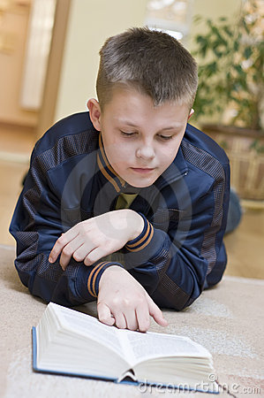 Boy reading book on carpet