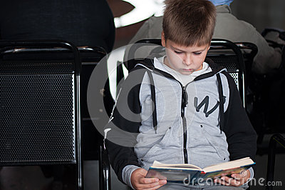 Boy reading  book at the station
