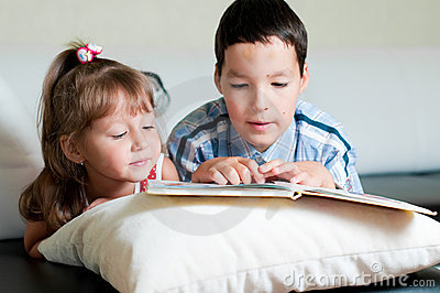 Boy reading a book to his sister