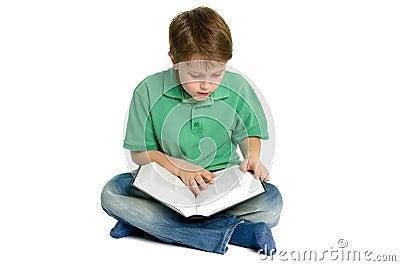 Boy reading crossed legs