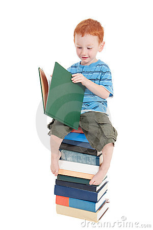 Boy reading kids book on stack of books