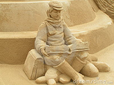 Boy reading in sand