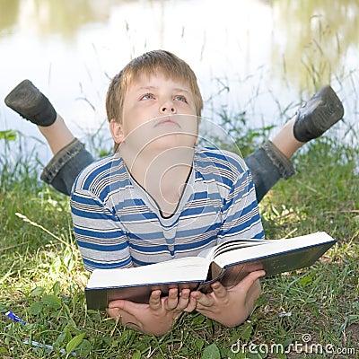 Boy reads a big book