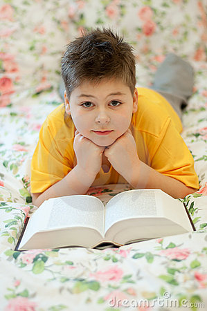 boy reads a book in bed