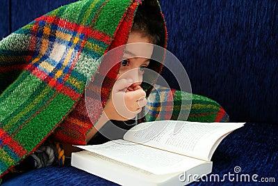 Boy reads book under blanket