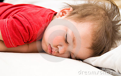 Boy in red dress sleeping on bed