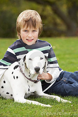 Boy Relaxing Outdoors With Pet Dog
