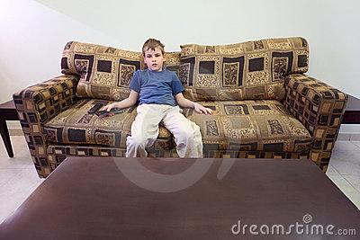 Boy with remote control sitting at sofa in room