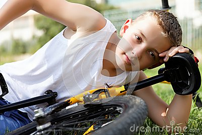 Boy rests with the bike